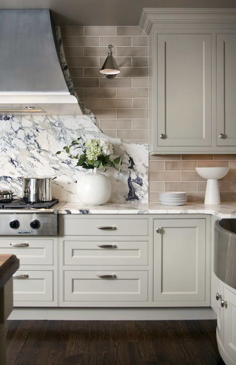 creamy sage cabinets with marble countertops and organic cut stove backsplash. Love the subway tile too!