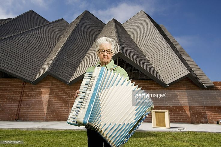 Stock Photo : Elderly woman with accordion in front of church, portrait