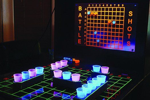 """Battleship Drinking-Popular Science says it is cool!....""""Sink Responsibly""""   Bored by beer pong, Kevin Kittle turned Battleship into a booze-infused board game.Kittle drilled holes in wooden ships to hold neon shot glasses. As in the real game, a player tries to guess the locations of his opponent's ships. If someone's vessel takes a hit, he must do a shot. Kittle suggests using tonic-infused concoctions, because quinine glows in ultraviolet light. Sink responsibly."""