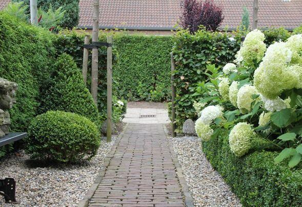 Allée en pavés bordée par des graviers, puis petite haie de buis avec derrière des hortensia. Tout simplement magnifique!!!