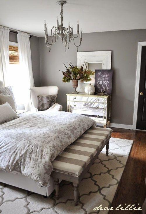 decoração de quarto com tapete cinza , parede cinza, banco nos pés da cama e lustre com lampadas em formato de velas