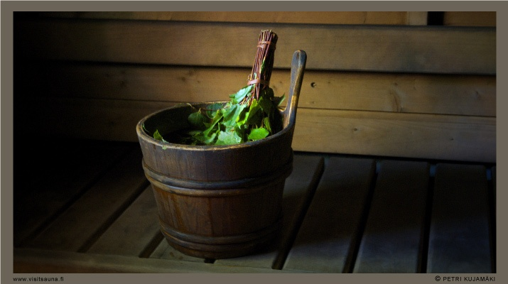 A vihta in a water bucket in a Finnish sauna