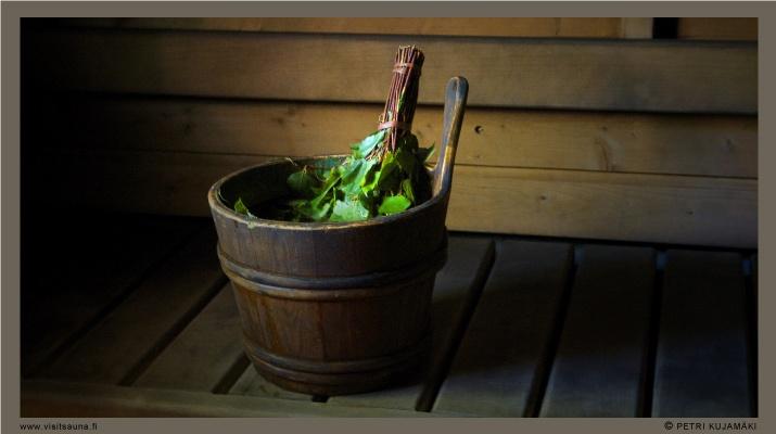 A vihta in a water bucket in a Finnish sauna