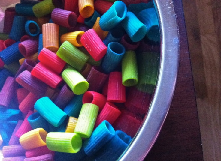 """Dye pasta (little bit of white vinegar in a bowl, food colouring drops & mix in the pasta, lay on parchment lined pan to dry over night) in bright colours - use for threading & sorting ("""",)"""
