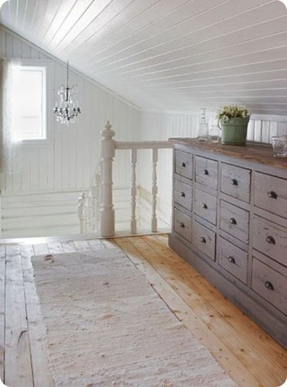 under the eaves: white painted paneling and pale blue dresser