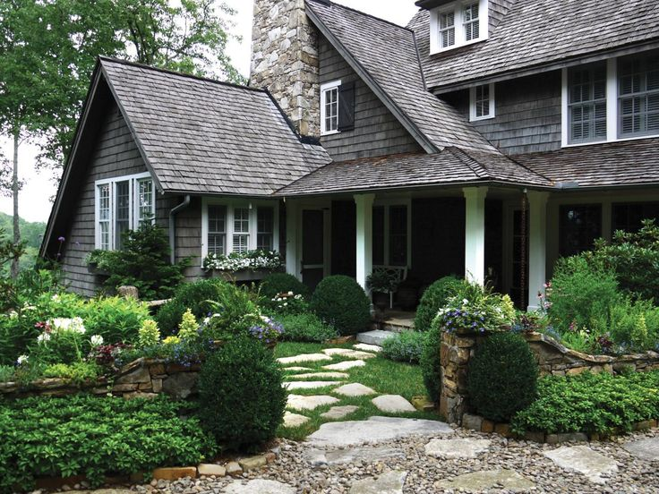 Stepping stones make for a quaint, cottage-style entryway to this gray shingled house with a flower garden in the front yard.