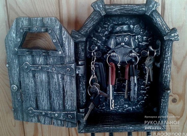 """Ключница """"За дверью"""" Ключница выполнена в виде старинной массивной двери,за которой вас ожидает домовой,всегда готовый взять на ответственное хранение пару связок ключей.Помимо этого есть два крючка на боковых стенках и предусмотрен ряд из 4х крючков снизу.На них могут располагаться как ключи,так и другие предметы:или зонт,или рожок для обуви, или щётка и т.п. Отлита полностью из алюминиевого сплава методом """"по земле"""",что придаёт изделию эффект старения.Вес изделия ~1,6 кг…"""