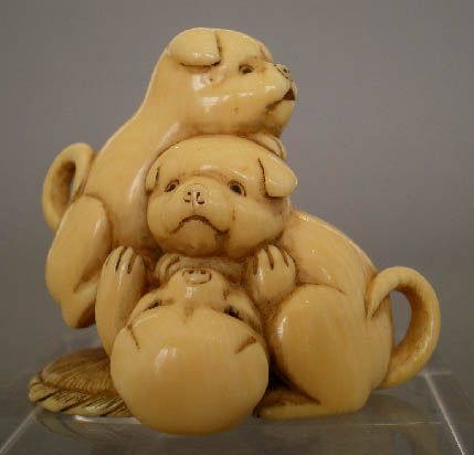"Three akita puppies playing on a round straw mat. Ivory. 19th century.  Illustrated in Bernard Hurtig's ""Masterpieces of Netsuke Art,"" p.41, fig.82,   as one of the netsuke from the Raymond Bushell collection.  Height: 1 1/2 inches.  Signed: Sekko (can also be pronounced ""Sekiko"").  Antique netsuke - Ivory."