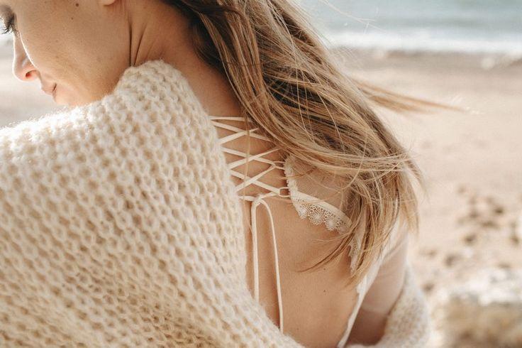AMBRE CHARME AUDACIEUX La femme Elisa Ness, mariée des temps modernes, conquérante, à la sensualité chuchotée, s'assume dans une combinaison aux découpes audacieuses et ajustées.  Enveloppée par une écharpe en maille oversize, ou par une cape en tulle rebrodé laine, elle ne craint pas le froid.