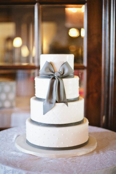 """Gray bow wedding cake.  I love the swiss dot-esque detail in the frosting.  Hope this isn't too close to violating Mike's """"nothing metallic on anything edible rule"""".  (Said rule announced after he saw a few of the other cakes I've pinned recently.)"""