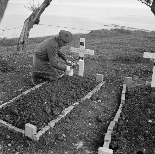 Private Ralph Forrester of the Seaforth Highlanders of Canada places flowers on the grave of his brother killed in Ortona, s the River Garig...