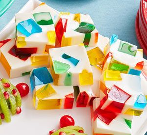 "Jewel Box Jigglers:   4 - 6 3 ounce boxes jello, various colors (avoid purple)  2 envelopes unflavored gelatin  14 oz can sweetened condensed milk Make jello and refrigerate. When firm, cut into cubes, put in lightly oiled glass 9X13., refrigerate. In a bowl, add unflavored gelatin and 1/2 c cold water, sit for 2 min., add 1 1/2 c boiling water, stir til dissolved. Stir in condensed milk. Refrigerate for 30 min. Slowly pour milk mix over cubes. Refrigerate overnight. Slice into 2"" squares;"