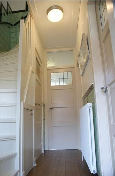 Trap met tegels en panel deuren in deze gang te zien