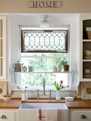 shelf in window and leaded glass window ... farmhouse sink and wood countertops... with a peak of open shelving and white dishes... what's not to love