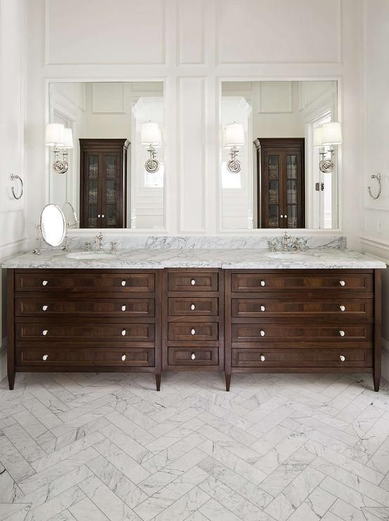 Sophisticated bathroom features a wall clad in decorative wall moldings lined with framed mirrors lined with sconces placed over a walnut stained double washstand topped with gray honed marble alongside a white marble herringbone tiled floor.