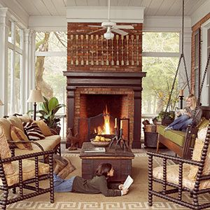 Cozy Screened Fall Porch  A wood-burning fireplace is the center of attention in this porch, and dozing, reading, and chatting are the orders of the day. An indoor-outdoor rug softens and defines the gathering space. The seating arrangement includes a upholstered swing that the homeowner had custom made based on an antique bench she saw at a Paris flea market.