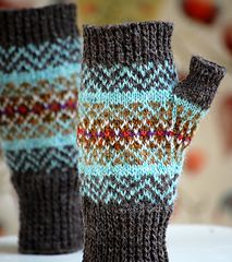 Perfect for fall, these little fair isle mitts are knit in shades of rust, brown and cream, with flashes of purple and orange, set against a background of turquoise blue. They have a thumb gusset and there are charts for left and right hands. One size to fit woman's hand circumference 7-7.5 inches (18-19 cm).