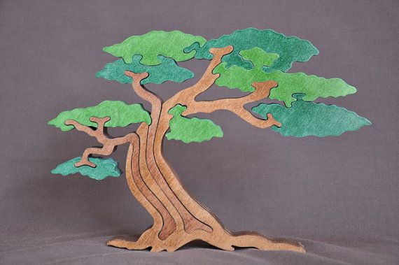 This handcrafted wooden puzzle measures 9 1/2 inches across by 6 1/4 inches tall. It is 3/4 of an inch thick and is free standing. This listing is for the GREEN tree.  The puzzles are finished on both sides with a non toxic finish. They come to you in shrink wrap for protecting the puzzle.  This tree can also be ordered in Summer colors. Convo me to order.