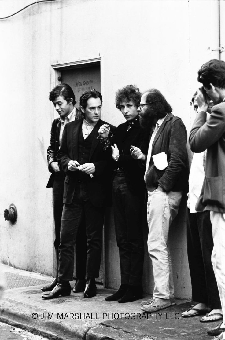 "From left to right: Robbie Robertson, Michael McClure, Bob Dylan, Allen Ginsberg in the alley (now Jack Kerouac Alley) between Vesuvio Café and City Lights bookstore. Larry Keenan is the photographer at right shooting images for use in Dylan's ""Blonde on Blonde"" album that were not used for that project."