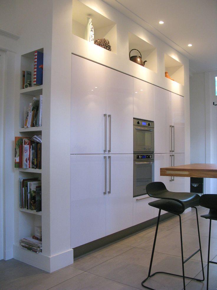 Om deze kastenwand in de keuken zit een ombouw waar aan de bovenkant en aan de zijkanten vakken in zijn gemaakt. Niet alleen heel handig voor je kookboeken en kookspullen maar het maakt de wand ook…