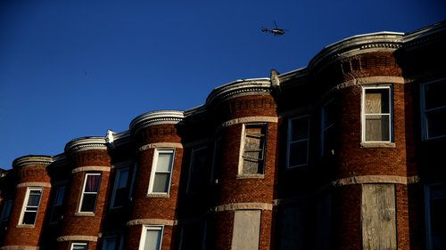"Ghettos in USA. A helicopter flies over a section of Baltimore affected by riots. Richard Rothstein writes that recent unrest in Baltimore is the legacy of a century of federal, state and local policies designed to ""quarantine Baltimore's black population in isolated slums."""