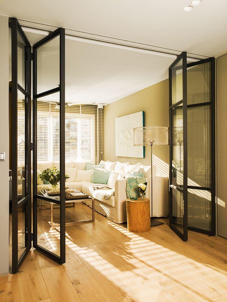 Salón en tonos claros separado del resto de la casa por una puerta con acordeón negra con cristales_00397867