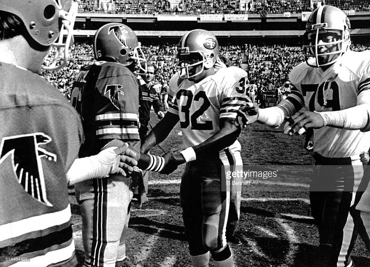 O.J. Simpson #32 and Al Cowlings #79 of the San Francisco 49ers greet Jim Mitchell #86 and Greg Brezina #50 of the Atlanta Falcons on December 16, 1979 at Atlanta-Fulton County Stadium in Atlanta, Georgia. The Falcons defetated the 49ers 31-21 in Simpson's last career game.