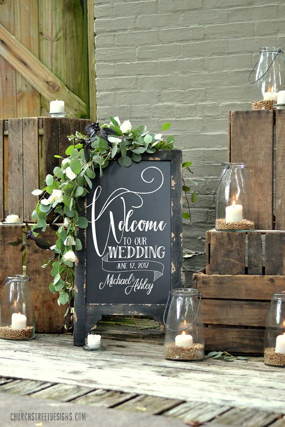 This beautiful double sided chalkboard comes with the Welcome To Our Wedding message permanently painted with a WHITE weather resistant paint, on one side of this sign. - CUSTOMIZE IT - Send us your names and date when ordering and we will permanently paint these onto the sign for FREE, making it a one-of-a-kind piece for your wedding.  The back side of the chalkboard is left blank so that you can easily add any addition messages or reception details with a chalk marker. This black, rustic…