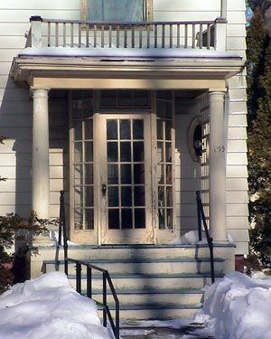 Enclosed vestibule at an entrance door on a columned porch.
