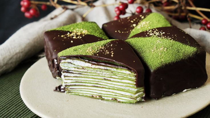 Recipe with video instructions: Chocolate-covered crepe cakes and gold flakes together? It's a matcha made in heaven.  Ingredients: 3 eggs, 380cc milk, 22g sugar, 135g flour, 15g matcha powder, 25g butter, melted, 1 tsp baking powder, 200cc heavy cream, 25g granulated sugar, 1 tbsp rum, chocolate, melted, matcha, gold leaf