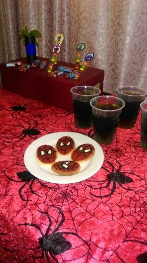 Superhero birthday party food ideas. Spider-Man biscuits, superhero colored layered jelly, green kryptonite snakes
