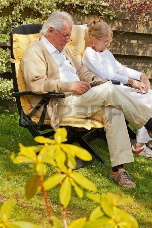 Pareja de ancianos sentados en el jardín leyendo un libro. El horario de verano. Foto de archivo - 19797009