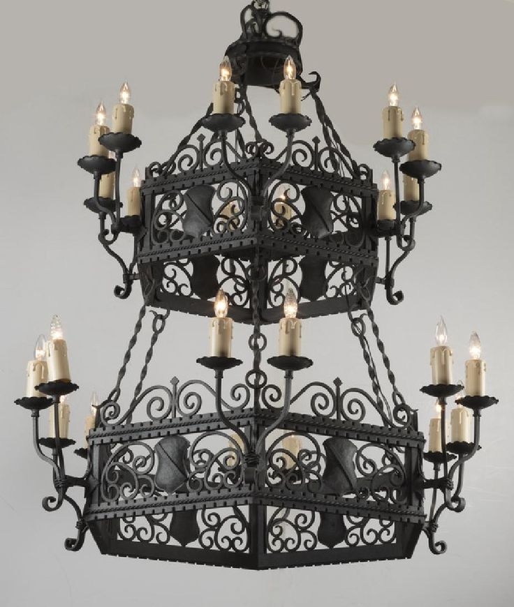 """Continental Gothic Revival style two-tier wrought iron 24-light chandelier, having a crown with tendrils issuing chain and twisted bar link supports, suspending two tiers of octagonal frames filled with shields interspaced with scrollwork, the exteriors each having six double candle sconces ending in faux candles for a total of twenty-four lights, 62""""h x 33""""dia."""
