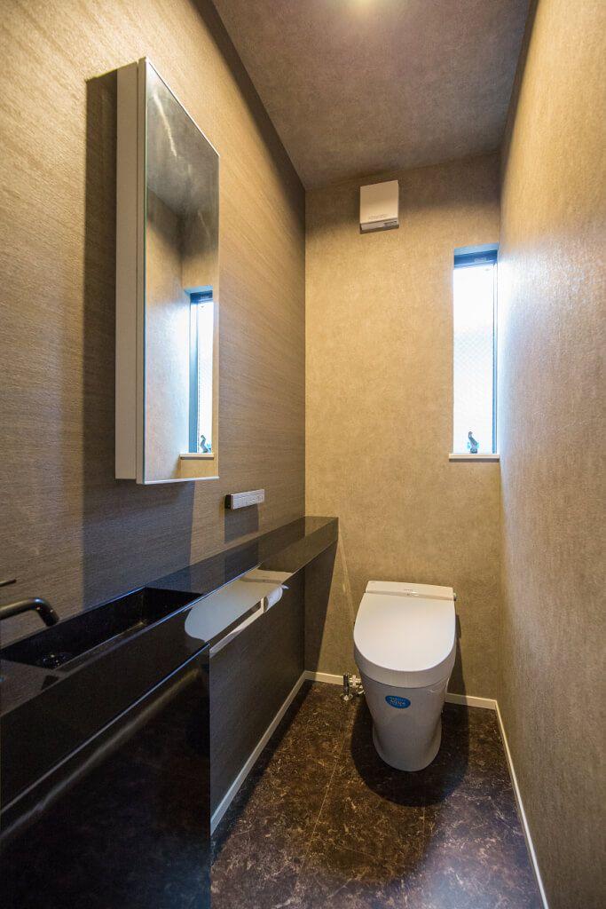 トイレ シックに濃色でまとめたトイレ 大理石調の床とブラックの