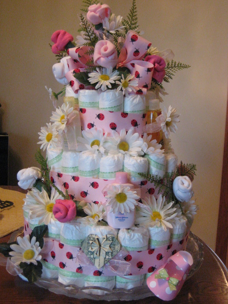 Baby Shower Diaper Cake with travel size baby products, roses from baby socks and dollar origami heart.