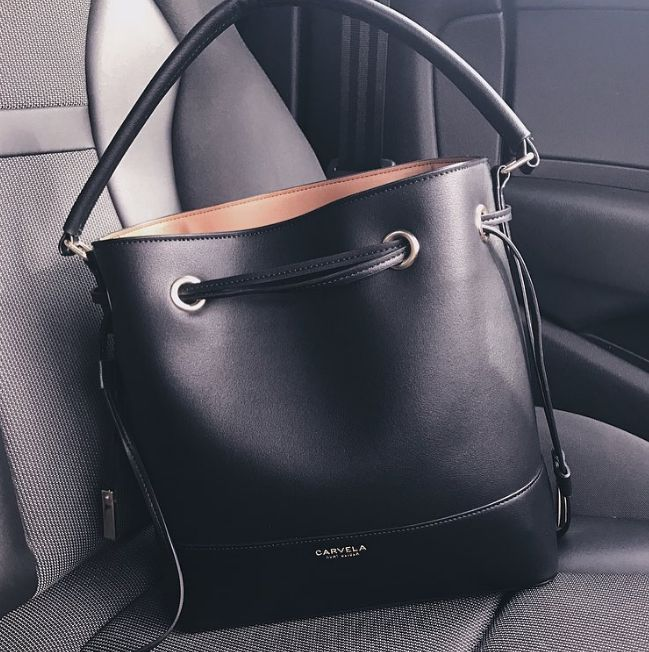 Set in black to go with everything, Carvela Kurt Geiger's Phoebe Bucket Bag is a new-season must. Featuring gleaming porthole details at the top, this versatile option is finished with both a top handle and a shoulder strap.