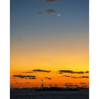 The Statue of Liberty stands tall underneath a crescent moon.