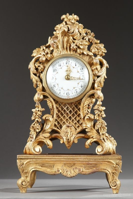 A small gilt wood mantle clock in Louis XV style richly decorated with foliage, lattice, garlands of flowers and fruits. The white enameled dial with Roman numerals and openwork pin is hightened with polychromatic garlands of flowers. Our clock rests on four foliated scroll feet above a rectangular pedestal adorned with shell.