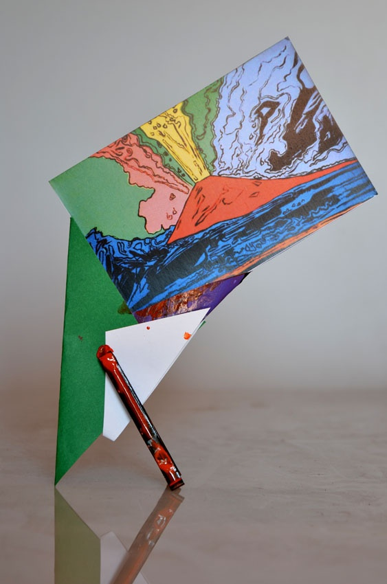 Photo-frame obtained by folding a sheet of recycled card so as to form the shape of a flattened inverted cone that sits stably thanks to a painted wooden clothes-peg. A photograph, or postcard of the museum just visited, is placed in the cone and remains suspended vertically like a leaf carried by the wind. Designed by Riccardo Dalisi for the Museo Nazionale di Capodimonte, Naples.