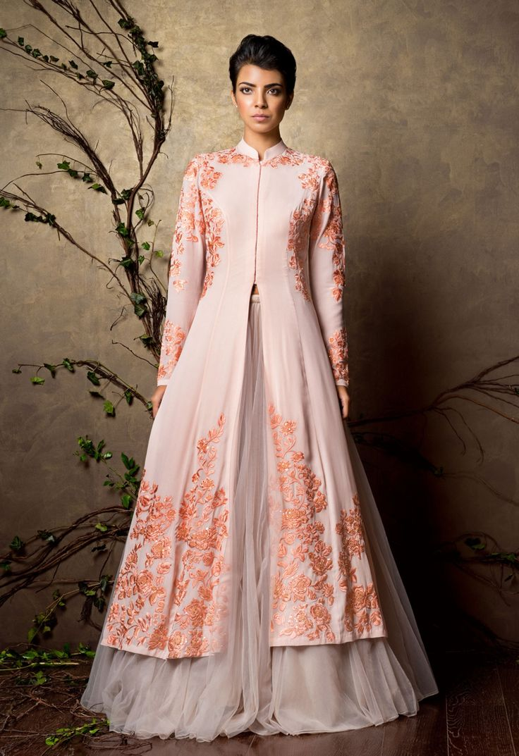 An elegant peach pearl silk georgette jacket with satin thread embroidery placed beautifully. It is worn over voluminous tulle lehenga that gives it a crisp and sophisticated feel.