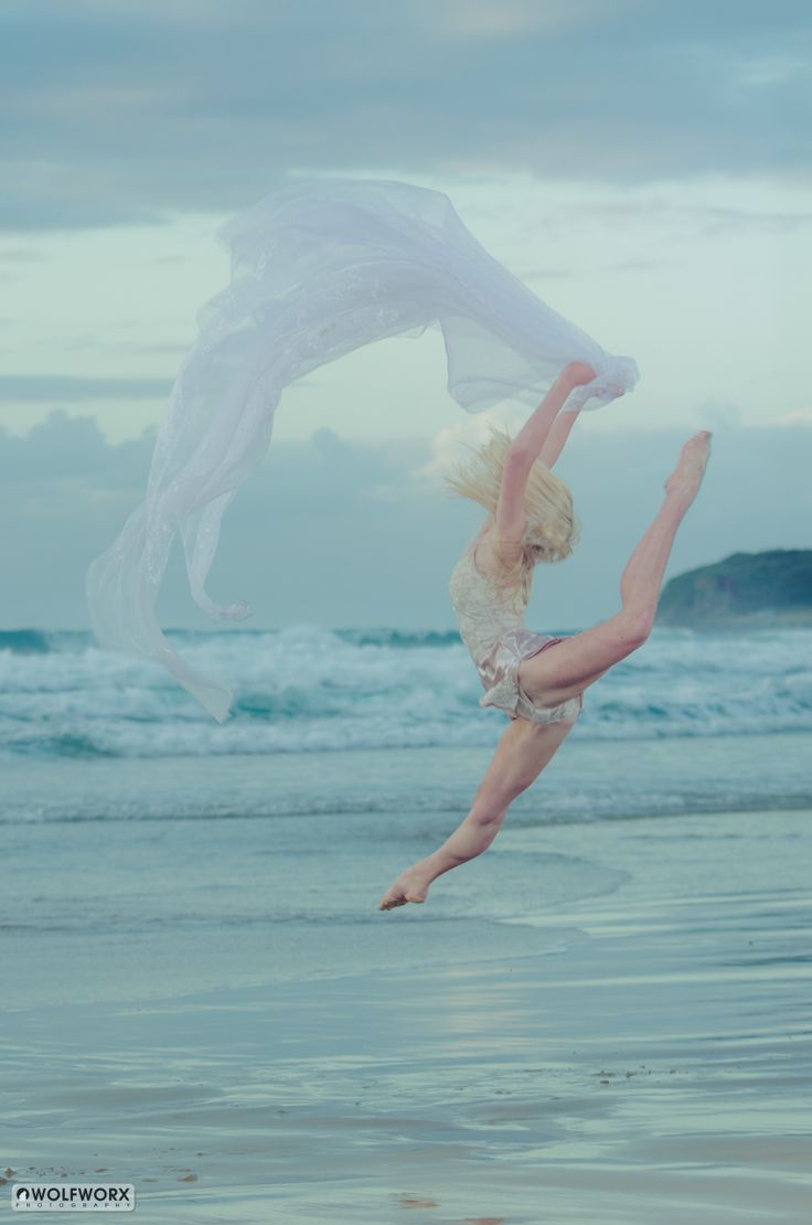 Beautiful dancer jumping on the beach with the ocean as a backdrop