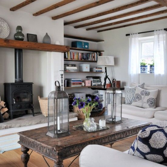 The wooden beams in this living room combined with the log stove give it a really cosy feel. The neutral furniture is combined with dark wooden touches and splashes of blue.