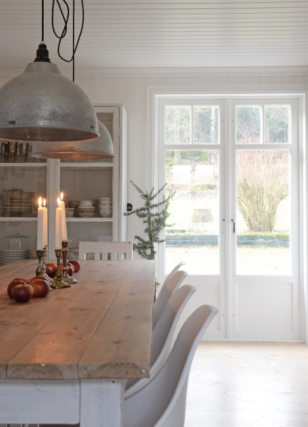 Anna Truelsen stylist. White interior kitchen dining candles industrial pendant lights white floor open shelving wood table