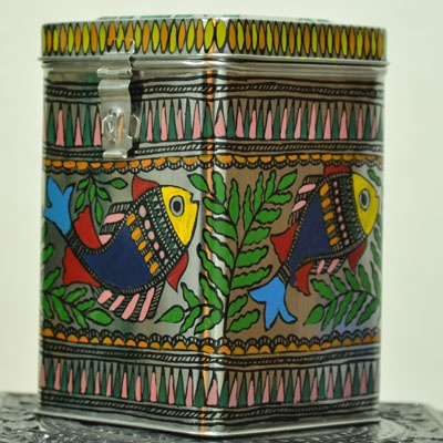 """Madhubani painted Tin Canaster- ideal for storage in the kitchen or other knick knacks.Beautiful, Unique & Durable - Madhubani painted Tin Canaster- ideal for bulk storage in the kitchen or linen or warm clothes .This art form depicts traditional stories painted by women on walls in Mithila, Bihar celebrating weddings, births and festivals.  Size - 9""""X6""""X6"""""""