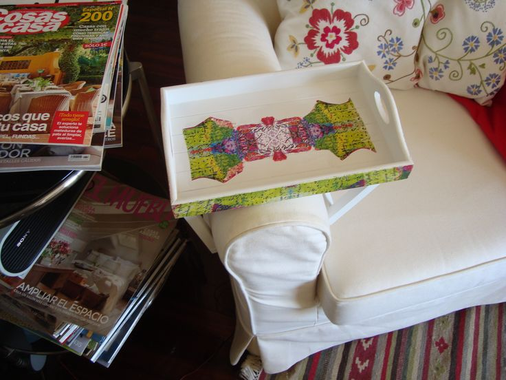 A wood sofa tray with a colorful decor.