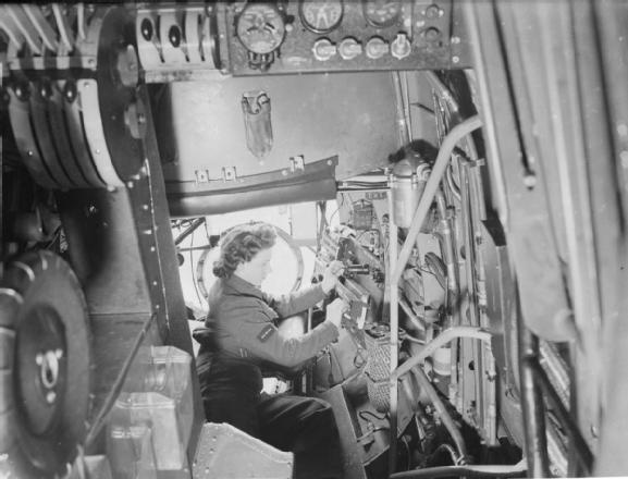 A WAAF electrician making an adjustment to the bomb switch units of a Lancaster bomber.