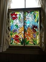 Vintage flower window: Use stained glass scraps, and cut them with a glass cutter. Then lay the pieces out on the window and play with them until happy with the pattern, then glue them down with 100% silicone and wait 24 hours to dry.  Use sanded grout from the home improvement store, black grout is a good color of choice, it just makes the colors POP.