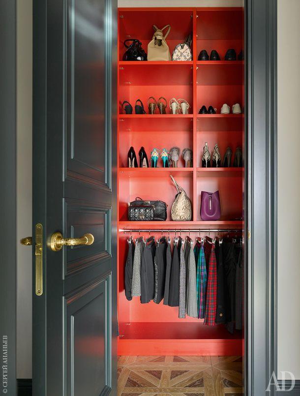 Полки и стены хозяйской гардеробной, расположенной в прихожей, выкрашены в ярко-красный цвет.