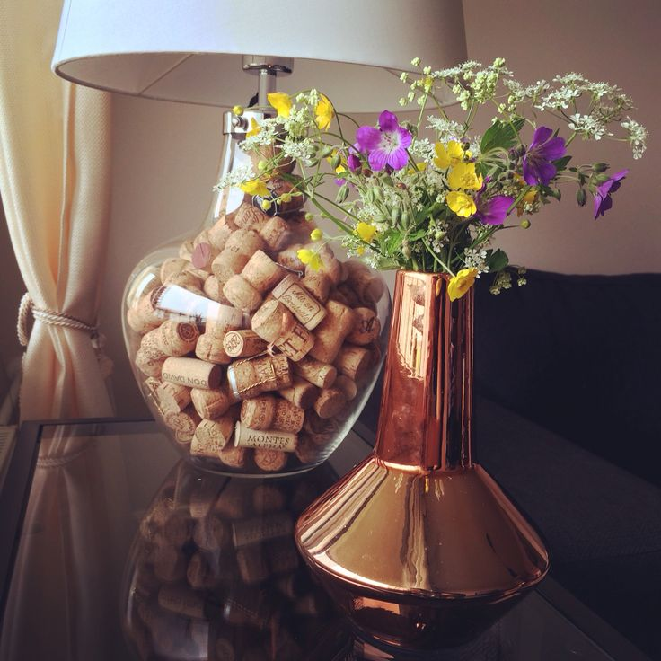Home favourites glass lamp filled with corks and copper vase with Finnish wildflowers