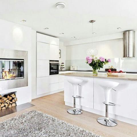Lyst og åpent kjøkken med øy og helt uten overskap. Innbydende med peis så nærme kjøkkenet #kjøkkeninspirasjon #miele #kjøkkenglede #nyttkjøkken #kjøkken
